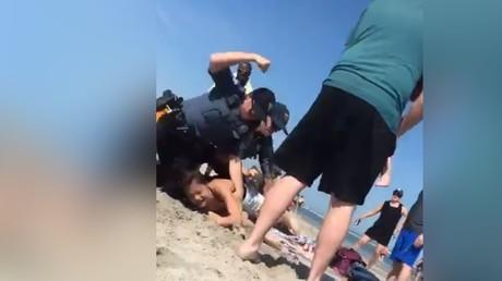Sur une plage du New Jersey le 26 mai, la jeune Emily Weinman au sol, avant de prendre un coup de poing dans la tempe par un policier qui voulait l'interpeller car elle avait refusé de lui donner son identité.