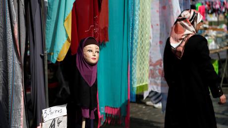 Une femme passe devant un mannequin portant un foulard sur un marché du quartier bruxellois de Molenbeek