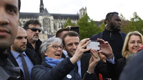 Candidat à l'élection présidentielle, Emmanuel Macron pose pour un «selfie» avec une partisane à l'extérieur de la cathédrale d'Amiens le 26 avril 2017, tandis que son garde du corps, surnommé Makao, monte la garde derrière eux.