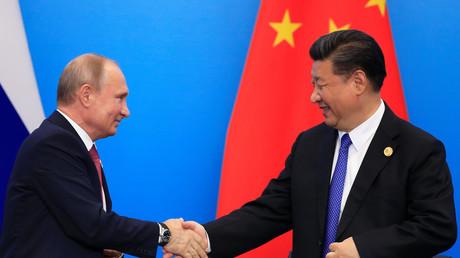 Le président chinois Xi Jinping salue Vladimir Poutine, le président russe, lors du sommet de l'Organisation de Coopération de Shanghaï (OCS) en Chine le 10 juin 2018