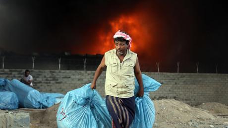 Un travailleur yéménite évacue des sacs de nourriture alors que le feu envahit l'entrepôt du Programme alimentaire mondial des Nations Unies (PAM) dans la ville côtière de Hodeidah le 31 mars 2018.