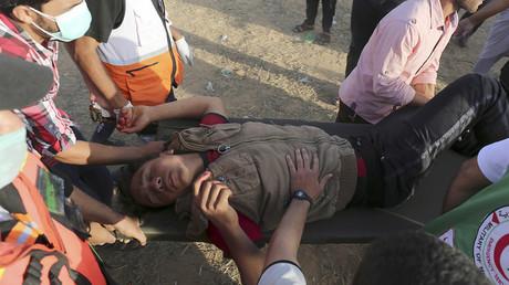 Des Palestiniens portent un blessé à la frontière entre Gaza et Israël, le 22 juin