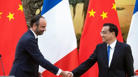 Poignée de mains entre les Premiers ministres français Edouard Philippe (g.) et chinois Li Keqiang (d.) le 25 juin 2018 au Palais du peuple à Pékin.