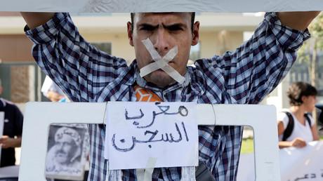 Un proche des leaders du mouvement Hirak, portant une pancarte sur laquelle est écrite prison marocaine.