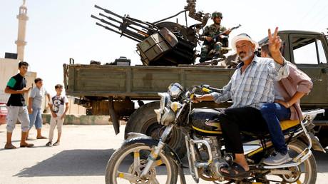 Illustration : un civil devant un véhicule blindé de l'Armée arabe syrienne, le 4 juillet 2018