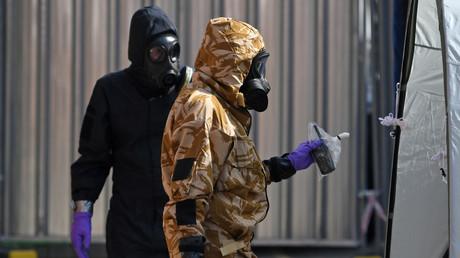 Un enquêteur portant une tenue de protection camouflée, des gants et un masque à gaz travaille avec un enquêteur de la police à Amesbury, au sud de l'Angleterre, le 6 juillet 2018