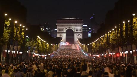 Les supporters célèbrent la victoire de la France devant l'Arc de Triomphe sur les Champs Elysées à Paris le 10 juillet 2018, après le coup de sifflet final du match de demi-finale de Coupe du Monde Russie 2018 entre la France et la Belgique.