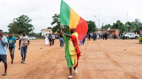 Un partisan du président sortant du Mali, Ibrahim Boubacar Keita, brandit un drapeau du Mali à Bouaké, le 22 juillet 2018