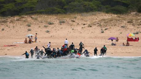 Des migrants débarquent d'un canot sur la plage