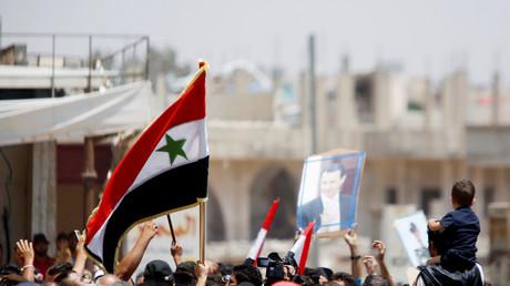 Des Syriens arborent le drapeau de leur pays ainsi qu'un portrait du président Bachar el-Assad à Deraa, le 4 juillet 2018 (image d'illustration).