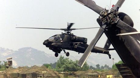 Un hélicoptère Apache de l'armée américaine survole la base d'opérations de l'armée américaine en Albanie le 6 juin 1999 (Image d'illustration).
