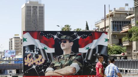 Deux Syriens passent devant un portrait de Bachar el-Assad à Damas, le 9 juillet
