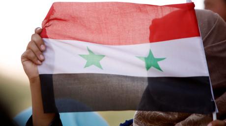 Un drapeau syrien brandi par une femme à Deraa.