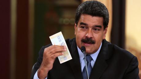 Le président vénézuélien Nicolas Maduro tient dans la main un billet de la nouvelle devise nationale : le bolivar souverain.