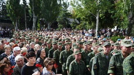 Soldats en uniforme et habitants sont côte à côte pendant la cérémonie d'adieu à Alexandre Zakharchenko.