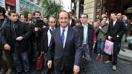 François Hollande, candidat du Parti socialiste (PS) aux élections présidentielles françaises de 2012, se promène dans une rue de Bordeaux, le 24 novembre 2011, accompagné de son garde du corps Alexandre Benalla.