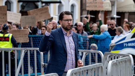 Le leader du parti anti-immigration SD Jimmie Akesson s'exprime le 31 août 2018, avec en arrière-plan des manifestants dénonçant la percée des nationalistes en Suède