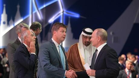 Le 3 octobre à Moscou, Vladimir Poutine sert la main de Ryan Chilcote présentateur du réseau de télévision publique américaine PBS, entouré (g.) de Francesco Starace, président du groupe énergétique italien Enel et (d.) de Khaled A. al-Faleh, ministre saoudien de l'Energie.