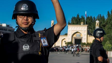 En Chine, un policier prévient de l'arrivée de musulmans à la mosquée Id Kah pour la prière de l'Aïd al-Fitr, dans la vieille ville de Kashgar, dans la région autonome ouïghoure du Xinjiang, le 26 juin 2017 (image d'illustration).