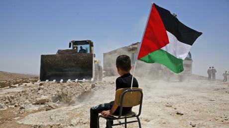 Un enfant assis et tenant le drapeau national palestinien assiste à la démolition par les autorités israéliennes d'un site scolaire dans le village de Yatta, au sud de la ville d'Hébron, en Cisjordanie, le 11 juillet 2018.