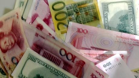 Des billets de dollars, d'euros et de yuans mélangés sur une table (image d'illustration).