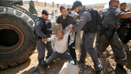 Des policiers israéliens arrêtent un Palestinien dans une manifestation contre le projet israélien de démolition du village bédouin palestinien de Khan al-Ahmar, en Cisjordanie occupée, le 14 septembre 2018.