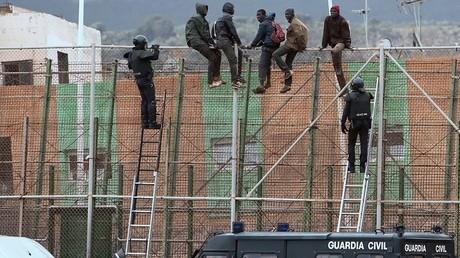 Des policiers espagnols venant chercher des migrants assis sur la clôture à la frontière de Melilla, en 2015.