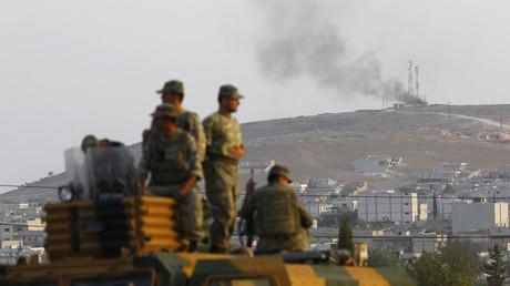 Des soldats turcs à bord d'un véhicule blindé, observant la ville syrienne de Kobané, le 3 octobre 2014.