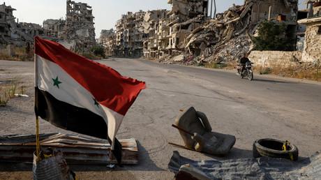 Le drapeau syrien flotte à un point de contrôle militaire dans la région d'Al-Khaldieh à Homs, en Syrie, le 18 septembre 2018.