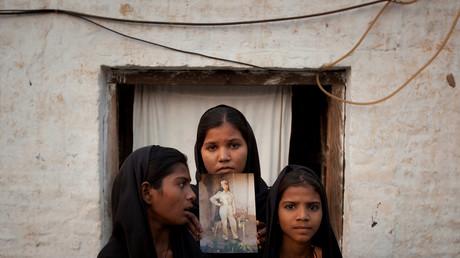Les filles d'Asia Bibi posant avec une photo de leur mère devant leur maison de Sheikhupura dans la province pakistanaise de Punjab en novembre 2010.