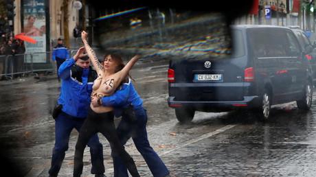 La police française maîtrise une militante Femen qui a approché, seins nus, le cortège du président américain alors qu'il arrivait sur les Champs Elysée pour participer à la commémoration du centenaire de l'Armistice à l'Arc de Triomphe à Paris, le 11 novembre 2018.