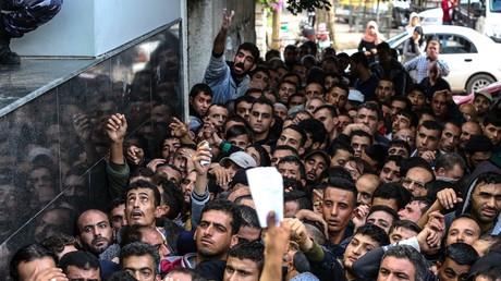 Des dizaines de Palestiniens attendent de recevoir une aide financière du gouvernement du Qatar pour les familles pauvres de la ville de Gaza, le 10 novembre 2018.