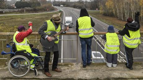 Des manifestants portant des gilets jaunes se tiennent sur un pont au-dessus de la route N70, le cinquième jour du mouvement contre la baisse du pouvoir d'achat et la hausse des prix, le 21 novembre 2018, près de Montceau-les-Mines, dans le centre de la France.