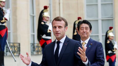 Le président français Emmanuel Macron  (au premier plan) et le Premier ministre japonais Shinzo Abe donnent une brève conférence de presse dans la cour de l'Elysée à Paris le 17 octobre 2018.