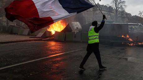 Un Gilet jaune brandit un drapeau tricolore devant une barricade à Paris, le 1er décembre.