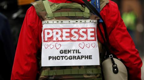 Un journaliste présent lors de la manifestation à Paris arbore un dossard avec des cœurs