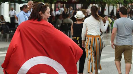 Une femme porte le drapeau tunisien lors d'une manifestation réclamant l'égalité des droits en matière de succession entre hommes et femmes, le 13 août 2018 (image d'illustration).