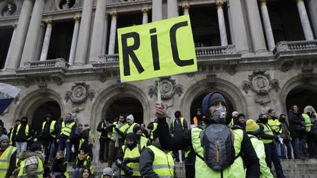 Un manifestant des Gilets jaunestient un carton pancarte portant l'inscription Référendum d'initiative citoyenne (RIC) devant l'opéra devant Paris, lors de l'acte V de la mobilisation des Gilets jaunes, le 15 décembre 2018.
