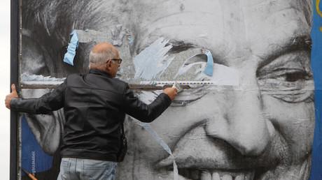 Un homme déchire un panneau du gouvernement hongrois dénonçant les activités de George Soros, le 5 octobre 2018 à Budapest.