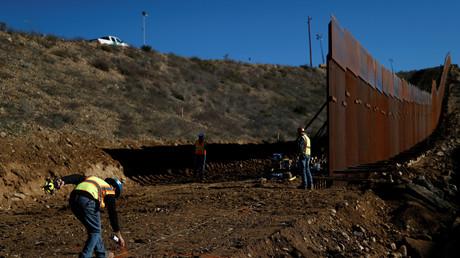 Des ouvriers tracent une ligne au sol alors qu'ils travaillent sur le mur à la frontière entre le Mexique et les Etats-Unis à Tijuana au Mexique, le 13 décembre 2018.