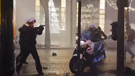 Un policier sort son arme pour maintenir des manifestants à distance lors de la mobilisation parisienne des Gilets jaunes, le 22 décembre 2018.