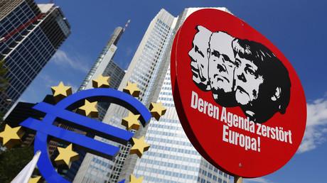 «Votre agenda détruit l'Europe» proclame une pancarte montrant la chancelière allemande Angela Merkel et d'autres responsables politiques européens lors d'une manifestation devant la Banque centrale européenne à Francfort le 8 juin 2013.