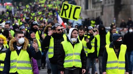 Un Gilet jaune brandit une pancarte en faveur du RIC (référendum d'initiative citoyenne en toutes matières), à Nantes, le 29 décembre.