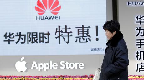 Une femme passe devant un magasin vendant des articles Huawei et Apple à Pékin, en Chine, le 12 décembre 2018.