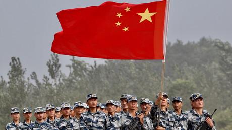 Des militaires chinois porte le drapeau national lors d'une cérémonie à Guangshui, dans la province du Hubei, le 30 juillet 2017.