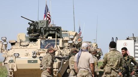 Des militaires américains discutent avec des combattants des YPG à Darbasiya en Syrie.