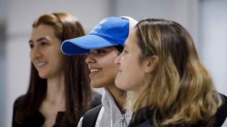 Rahaf Mohammed al-Qunun (centre), à l'aéroport de Toronto, à côté du chef de la diplomatie Chrystia Freeland (droite)
