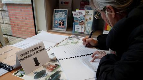 Une femme écrivant sur un cahier de doléances dans la commune de Grand Bourgtheroulde le 14 janvier (image d'illustration).