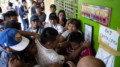 Des Philippins attaquent un votant accusé de bourrage d'urnes durant un vote dans la province de Cotabato dans le sud des Philippines, lors du référendum pour créer une région autonome pour les musulmans, plus vaste et dotée de davantage de droits que la précédente, le 21 janvier.