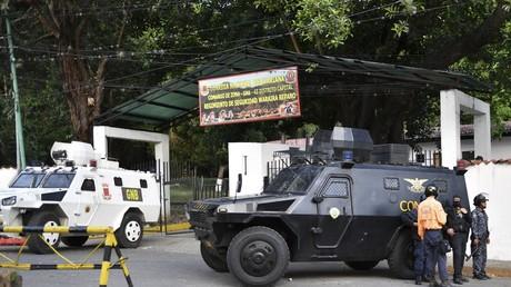 Des voitures blindées stationnent devant le quartier général de la Garde nationale bolivarienne de Cotiza à Caracas, après l'appel à la rébellion d'un groupe de militaires contre Nicolas Maduro,  le 21 janvier 2019.